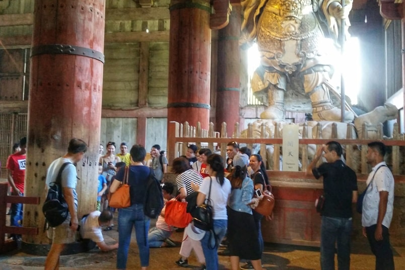 Best UNESCO world heritage sites to visit in Nara. Wooden pillar column with hole. Great Buddha nostril size. Great Buddha hall at Todaiji temple. Backpacking Japan