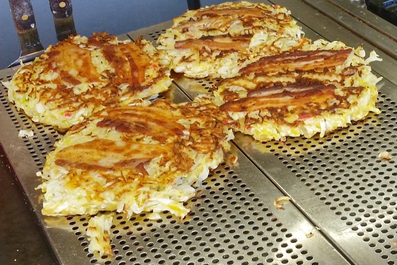 Okonomiyaki - street food in Japan. Best okonomiyaki in Osaka or Hiroshima. Backpacking Japan foodie travel