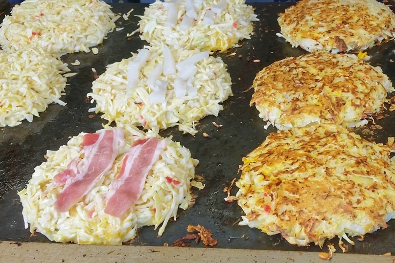Okonomiyaki with pork, with squid. Street food in Japan. Best okonomiyaki in Osaka or Hiroshima. Backpacking Japan foodie travel