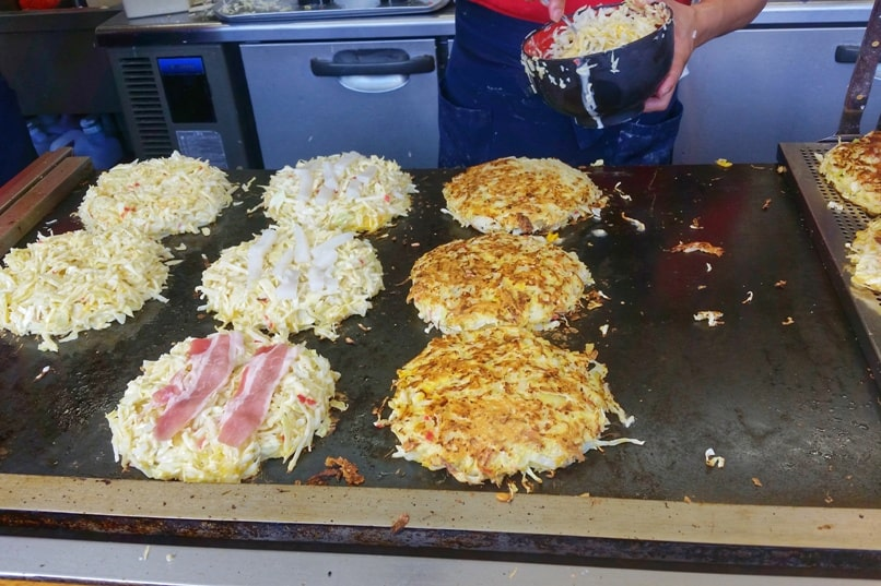 Okonomiyaki, with pork, with squid - street food in Japan. Best okonomiyaki in Osaka or Hiroshima. Backpacking Japan foodie travel