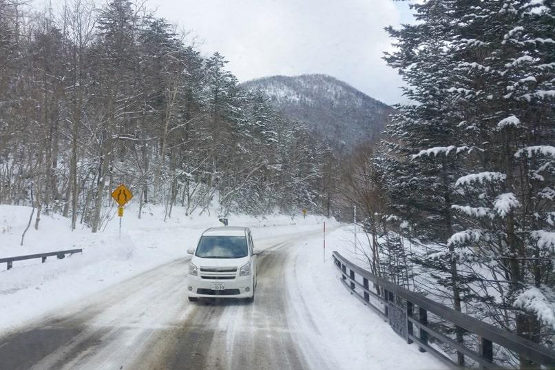 Sapporo to Lake Shikaribetsu igloo village: Snow Hokkaido roads on bus to Lake Shikaribetsu. Backpacking Hokkaido Japan winter