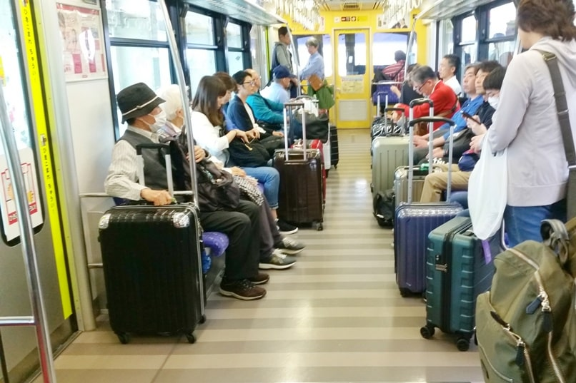 Okinawa monorail at Naha Airport - yui rail train seats with luggage, big suitcase, carry-on, backpack. Backpacking Okinawa Japan