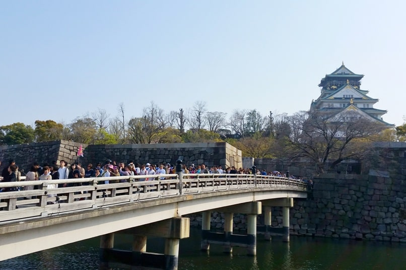 Osaka castle with cherry blossoms - how to get there gokurakubashi bridge - near jr station osakajyokoen station osaka loop line - things to do in osaka to see cherry blossoms. Backpacking Osaka Japan