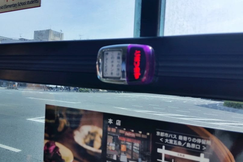 Getting around Kyoto by bus. how to take kyoto bus. button for next stop. Backpacking Japan travel blog