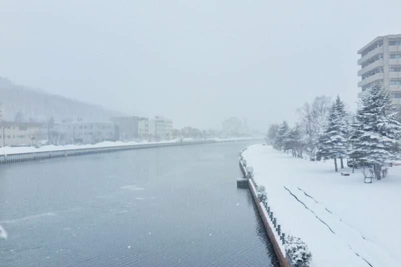 Hokkaido Japan winter itinerary with 7-day JR Hokkaido pass. Walk from Abashiri station to abashiri drift ice cruise port walk along river. 2 days in Hokkaido. Backpacking Japan winter travel blog