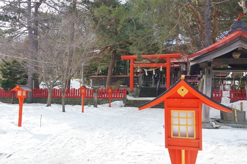 Hokkaido Japan winter itinerary with 7-day JR Hokkaido pass. sapporo fushimi inari shrine red orange torii gates in winter. 5 days in Hokkaido. Backpacking Japan winter travel blog