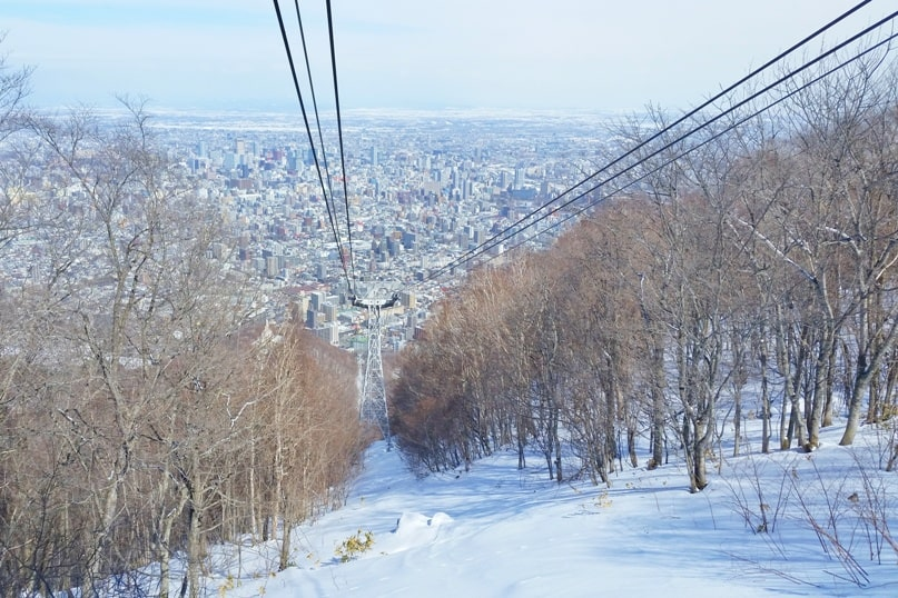 Hokkaido Japan winter itinerary with 7-day JR Hokkaido pass. sapporo mount moiwa ropeway observation deck in winter with sapporo city views. 5 days in Hokkaido. Backpacking Japan winter travel blog