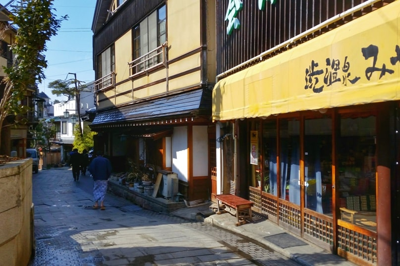 Walk the streets of Shibu Onsen hot springs village. 2 day Nagano winter itinerary with snow monkey pass. Backpacking Japan travel blog